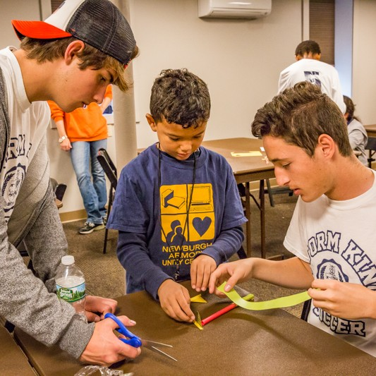 Eduardo Pena, left, and  Daniel Moreno, right, help their student build a rocket with straws